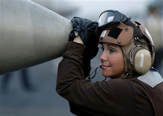woman in air force holding the nose of an airplane.  Smiling and wearing headphones and goggles